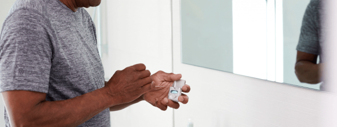 a man taking floss from the container in his bathroom