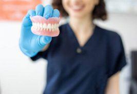 a dental hygienist holding up a model of teeth