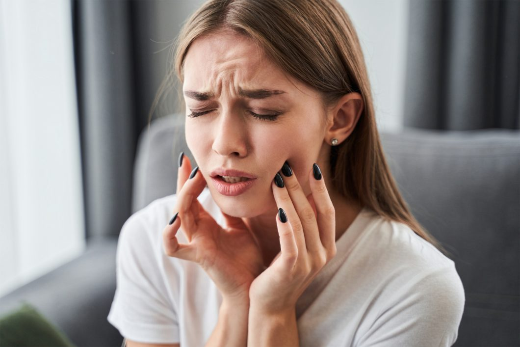 Young woman massaging her face because of tooth pain